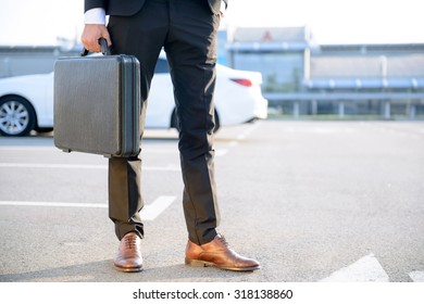 Ready to work. Modern stylish  businessman holding case and keeping hand in a pocket with his car standing on the background