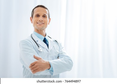 Ready to work. Proud medical specialist holding hands together on chest and keeping smile on his face while looking straight at camera