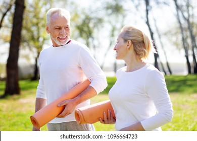 Ready for workout. Active healthy couple holding yoga mats while going together to the training