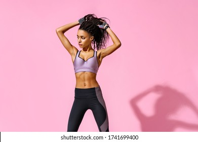 Ready to workout. Photo of african american girl with perfect body on pink background. Strength and motivation