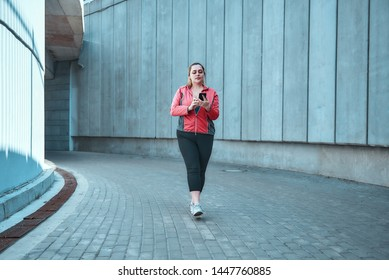 Ready for workout. Young plus size woman on sports clothes holding smart phone while standing outdoors.
