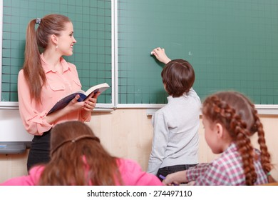 Ready to write. Young female smiling teacher and pupil standing at blackboard, pupil is going to write on blackboard.