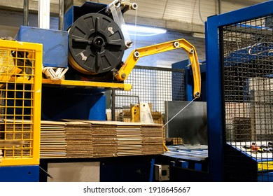 Ready-made cardboard boxes are moved in stacks along an automated packaging line. The strapping machine packs the stacks with thick white thread. Paper corrugated box factory.