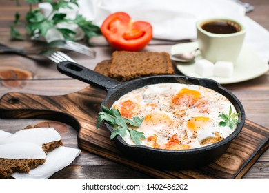 Ready-to-eat breakfast: shakshuka from fried eggs with tomatoes and parsley in a pan, bread with butter and coffeee on a wooden table