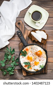 Ready-to-eat breakfast: shakshuka from fried eggs with tomatoes and parsley in a pan, bread with butter and coffeee on a wooden table. Top view