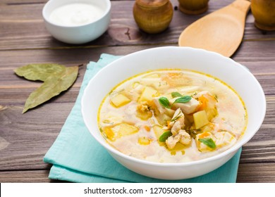 Ready-to-eat chicken soup with potatoes and herbs in a white bowl and sour cream on a wooden table