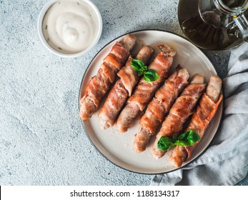 Ready-to-eat pigs sausages wrapped in bacon on plate. Fried savory sausages wrapped in bacon served fresh green basil leaves with sauce on background. Copy space for text. Top view or flat lay.