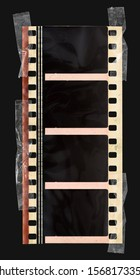 real 35mm movie filmstrip with soundwaves and empty blank dark frames on black background fixed by sticky tape snips. old film effect concept.