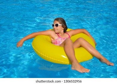 Real adorable girl relaxing in swimming pool, summer vacation concept
