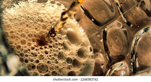 Real ale or beer being poured into a old pint pot viewed from above with bubbles and froth the colour of gold