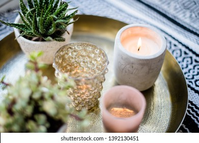 Real apartment interior decor, aromatic candles and plants on vintage tray with pillows and blanket on white windowsill