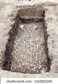 Real archaeological excavations. The remains of human bones (2 skeletons) with many artefacts in the tomb. The foot of archaeologist in sporty shoes. Measure tool. Outdoors, close up, copy space.