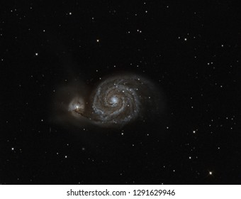 real astronomic picture taken with telescope and ccd of whirlpool galaxy, a spiral galaxy absorbing a smaller one