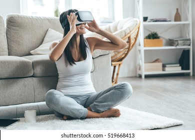 It is so real! Attractive young woman adjusting her VR headset and smiling while sitting on the carpet at home