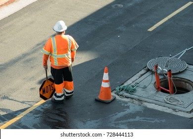 A real authentic construction flag person standing by manhole
