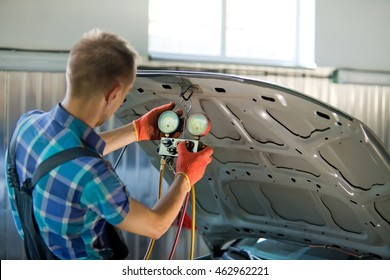 Real auto mechanic worker in garage. Auto service and diagnostic