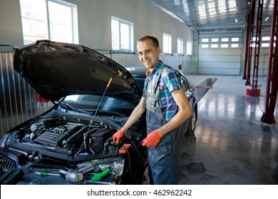 Real auto mechanic worker in garage.