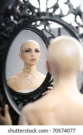 Real bald cancer survivor woman looking calmly into the mirror