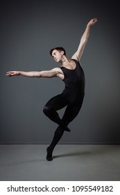 Real ballet dancer. Self-confident handsome concentrated man in a black tights dancing ballet in the dancehall holding up his hands and focusing on movement.