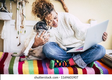 real best friends cheerful woman working at laptop on the terrace at home while hug her best love and friends  smiling dog pug sitting at his left. colorful and enjoyed concept image for couple