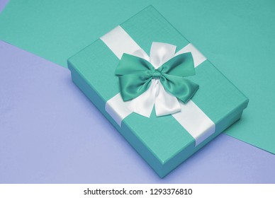 Real box with white and blue bow and ribbon top view on Valentine's day isolated on blue and purple background. Flat lay. Copy space