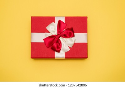 Real box with white and red bow and ribbon top view on Valentine's day isolated on yellow background. Flat lay. Copy space