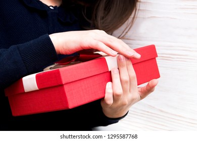 Real box with white and red bow and ribbon in girl s hands on Valentine's day isolated on white background. Copy space.