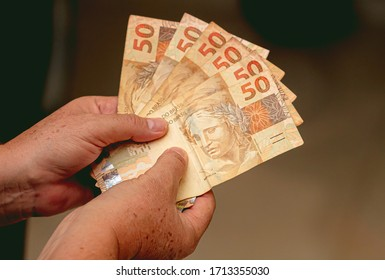 Real - Brazilian currency. Money, Dinheiro, Reais, Brasil, hand. Woman holding in hands a fifty Reais banknotes.