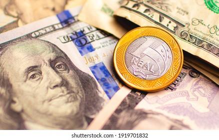 Real (BRL), money from brazil. Dinheiro, Brasil, Real Brasileiro, Reais. One real coin on US dollar bills. Photo representing the exchange idea.