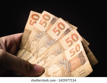 Real - BRL, Money from Brazil. Reais, Dinheiro, Brasil. A Man holding a brazilian banknotes in hand.