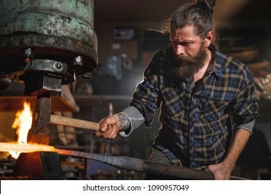 Real brutal blacksmith works in a workshop mechanical hammer with a red-hot iron. Portrait of a profession.
