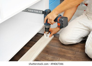 Real carpenter assembling new furniture