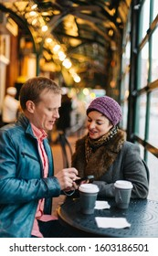 Real Caucasian couple in a cafe drinking coffee and using a handheld smartphone device