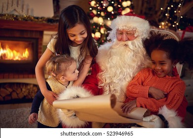 Real Christmas father reading wish list with mixed race little girls