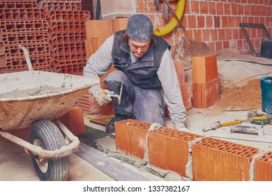 Real construction worker bricklaying the wall indoors.