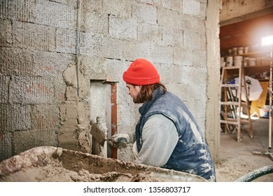 Real construction worker making a wall inside the new house.