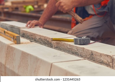 Real construction worker with measuring tape leveling concrete blocks.