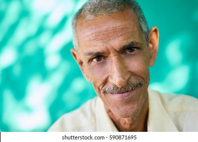Real Cuban elderly people and feelings, portrait of happy old hispanic man with mustache from Havana, Cuba looking at camera and smiling