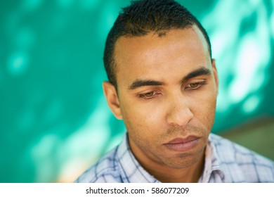 Real Cuban people and emotions, portrait of sad latino man from Havana, Cuba looking at camera with worried face and depressed expression