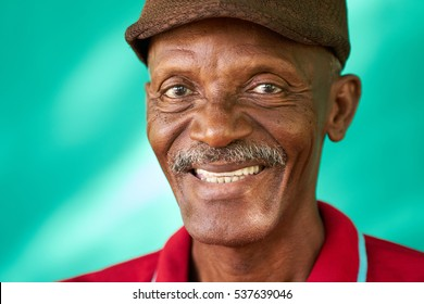 Real Cuban people and feelings, portrait of happy senior african american man looking at camera. Cheerful old latino grandfather with mustache and hat from Havana, Cuba