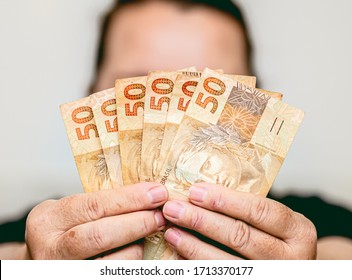 Real currency. Brasil, Dinheiro, Money, Reais. Woman holding in hands a fifty Reais banknotes.