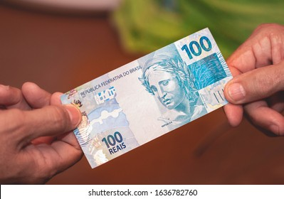 Real currency - Brazil. Dinheiro, Brasil, Reais, Hand, Real Brasileiro. Man pretending to pay another person with a hundred reais bill.