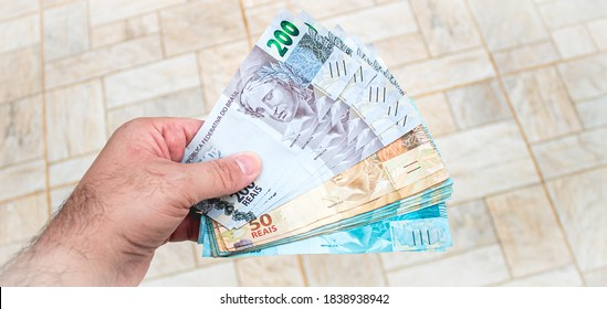Real currency, money from Brazil. Brasil, Dinheiro, Reais, Hand. People holding in hand a brazilian banknotes.