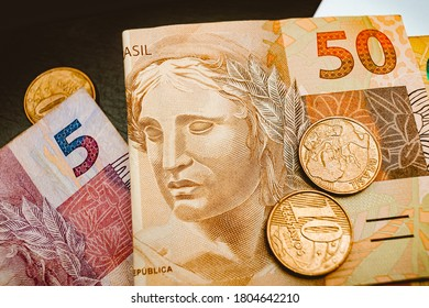 Real currency, money from Brazil. Dinheiro, Brasil, Reais, Real brasileiro. A group of brazilian banknotes and coins on a table.