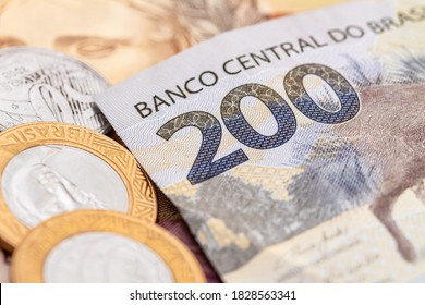 Real currency, Money from Brazil. Dinheiro, Reais, Brasil. A banknote of 200 reais and brazilian coins in close-up.