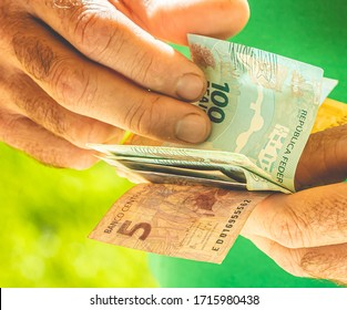 Real Currency. Money, Dinheiro, Brasil, Reais. Man holding in hand a group of Real banknotes.
