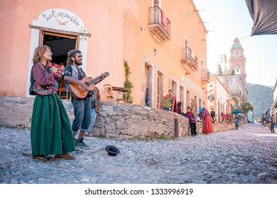 Real De Catorce / Mexico - July 13 2018 [a young couple of street performers are playing guitar and tambourine, busking for money]
