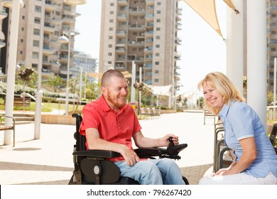 Real disabled man on the wheelchair have fun with pretty woman