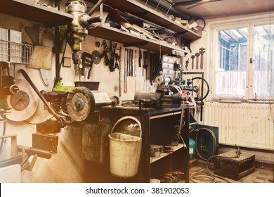 real domestic DIY home workshop full of tools, untidy, ready for work, detail of homemade lathe, retro vintage color tone