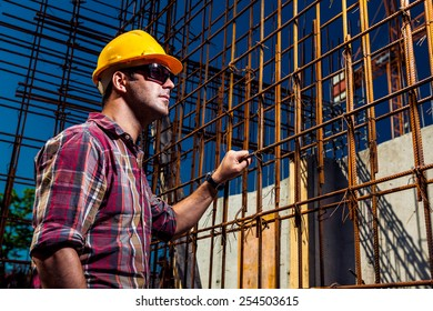 Real Engineer wearing protective gear and sunglasses supervising his construction site near reinforced steel concrete